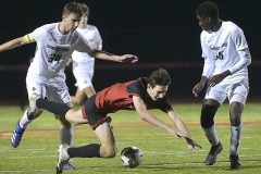 West Chester East senior (4) Ryan Cogill is tripped up going for goal as Spring-Ford's  (34) Trevor Jones and (35) Ekow Asomaning  defend in the first period. Spring-Ford went on to win 1-0 in District playoff action at West Chester East Thursday night.