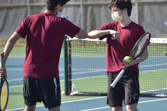 Conestoga's Manas Dhawan annd Basil Lubiniecki exchanges elbows after scoring a point against Unionville in doubles tennis Monday afternoon.