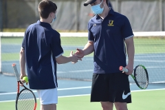 Unionville's Nate Butler and Will Poprick exchange fives after scoring a point in doubles tennis  against Conestoga Monday afternoon.