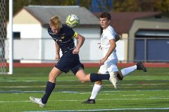 Unionville's (24) Alex O'Leary heads the ball on defense as Kennet's (4) Gavin Steele looks on. U went on to a 3-0 victory.