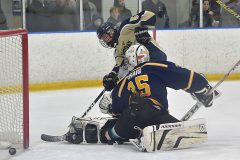 West Chester Rustin's (56) Aiden Harris puts puts the puck past Unionville goalie Keigan Craig in the 13th minute of the second period to break a scoreless tie at Ice Line Wednesday night.