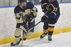 West Chester Rustin's (55) Alex Crook moves the puck ahead of Unionville's (73)Jay Kulp in the first period of Flyers Cup action at Ice Line Wednesday night.