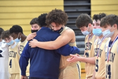 West Chester Rustin's (34) Jacob Barksdale embraces coach Keith Cochran as he distributes runner-up medals in the District 1 final against Chester.  Barksdale went out in the first quarter as Rustin lost lost62-46.