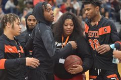 Nikera Brooks, mother of murdered Chester player Edward Harmon gets hugs and a basketball they wrote messages on from Chester players before the start of their PIAA state playoff game against Simon Gratz Wednesday evening at Cardinal O'Hara High School.