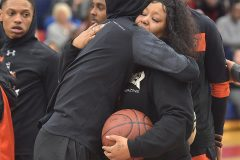 Nikera Brooks, mother of murdered Chester player Edward Harmon gets hugs from Chester players before the start of their PIAA state playoff game against Simon Gratz Wednesday evening at Cardinal O'Hara High School.