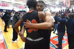 Chester's (5) Zahmir Carroll hugs teammate (30) Karell Watkins after Carroll hit the winning basket as time expired to defeat Simon Gratz in PIAA playoffs at Cardinal O'Hara High School Wednesday night.