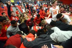 West Chester East players and fans mob a stunned Tym Richardson after he hit a three point shot with 1.8 seconds left on the clock to give the Vikings a 38-35 victory over Pottsville Tuesday evening at Reading High School in PIAA 5A playoffs.