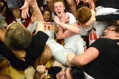 West Chester East players and fans mob a stunned Tym Richardson, (21) left, after he hit a three point shot with 1.8 seconds left on the clock to give the Vikings a 38-35 victory over Pottsville Tuesday evening at Reading High School in PIAA 5A playoffs.