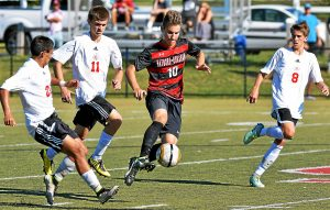 Bob Raines--Digital First Media Hatboro-Horsham's Nick Hatzenbeller sends the ball forward from midfield surrounded by Upper Dublin players Jose Palomeque, Collin Muth and Kevin Devlin Sept. 22, 2016.