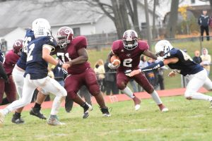 Chichester's Rashaad Smith rumbles ahead as Sun Valley's James Gines tries to wrap him up.