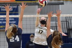 Unionville's (17) Maddy Lowe hits a shot between Council Rock North's (24) Julia Watson and (22) Katelyn Logan in the first game of theDistrict 1- 4A  volleyball finals at Unionville High School.